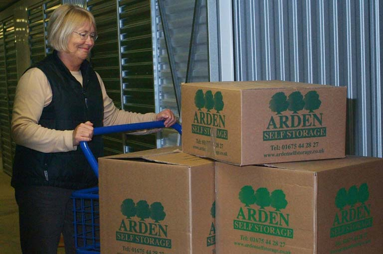 an image of a woman pushing Arden Self Storage-branded cardboard boxed on a blue trolley