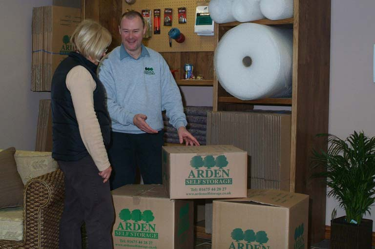 an image of an Arden Self Storage employee putting together branded boxes for a customer