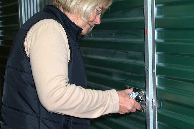 an image of a client using the padlock provided by Arden Self Storage to lock up their self storage facility