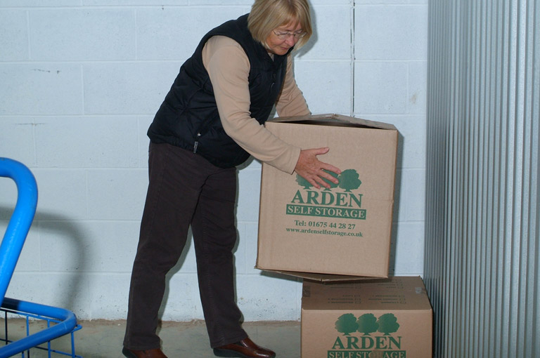 an image of a client placing Arden Self Storage-branded boxes into a storage unit they are renting from our self storage facility in Solihull
