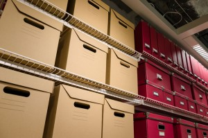 an image of different storage boxes and folders stacked upon metal shelving units