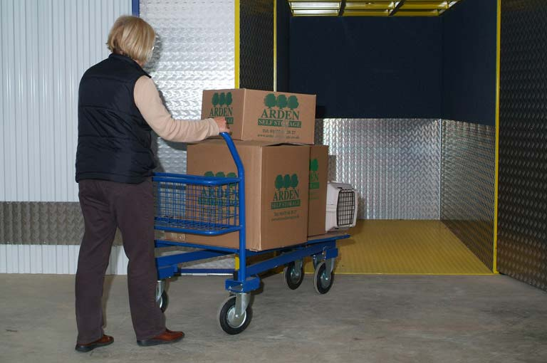 an image of a customer pushing their Arden Self Storage boxes into the storage lift at our facility