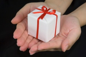an image of hands holding a gift box isolated on black background