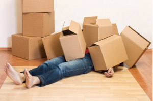 an image of a person lying under storage boxes