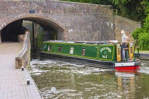 canal boat/ house boat on a river going under a bridge